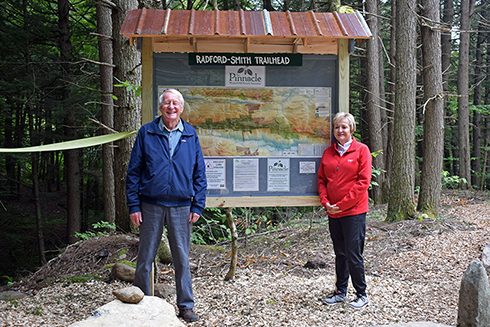 Terry and Edna Radford bracket the new trail kiosk created by Andy Toepfer.