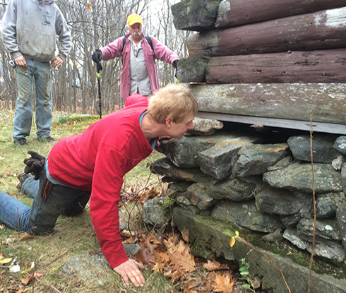 Master Carpenter Phil Pellerin inspects the foundation, where sections are missing stones and need repair or rebuilding.