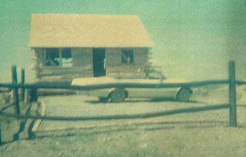 The original 1964 summer cabin had running water for the kitchen and bathroom.  The cosmopolitan convertible in the parking area proves the road to the cabin was quite passable.  No large trees are visible around the building.