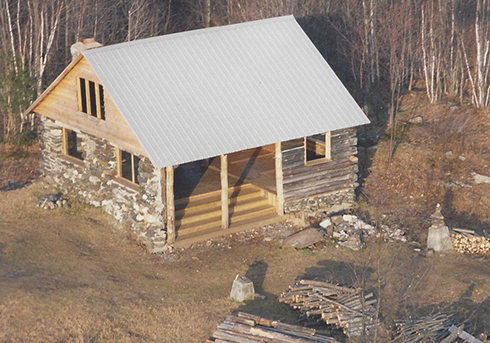 This aerial view of the south and west sides of the cabin-turned-shelter, renovated in 1999, show new western clapboards, a half-open south side with broad steps, and a new metal roof.