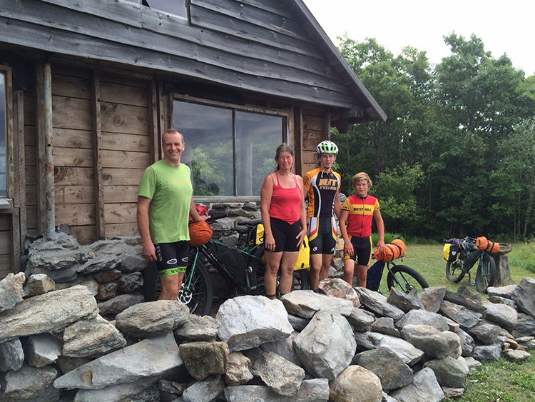 Bikers check out the progress on the renovation of the Pinnacle cabin's stone west wall.  In front of them lie the remaining stones that will complete the stone side of the building.